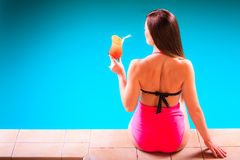 Girl s in swimsuit at poolside with cocktail glass back view. Royalty Free Stock Photography