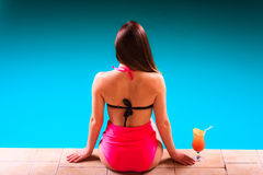 Girl s in swimsuit at poolside with cocktail glass back view. Royalty Free Stock Photo