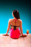 Girl s in swimsuit at poolside with cocktail glass back view. Royalty Free Stock Image