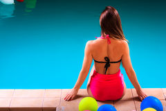 Girl s in swimsuit relaxing at poolside back view. Royalty Free Stock Photo