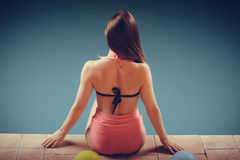 Girl s in swimsuit relaxing at poolside back view. Stock Images