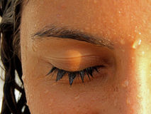 Girl's wet eye after swiming. A girl's closed eye in macro mode, after taking a swim in the water Royalty Free Stock Photos