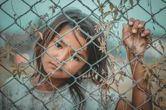 Girl's White and Gray Crew-neck Top Holding Gray Wire Fence royalty free stock photos