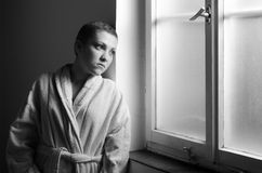Girl, sad cancer patient looking through hospital window. In black and white Stock Photos