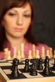 Girl with the sad looks on the chessboard Royalty Free Stock Photo