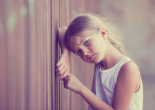 Girl sad portrait. Girl in elementary school age looking depressed outdoors in park Stock Photography