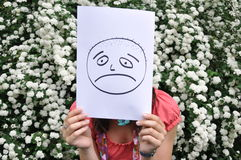 Girl with sad smiley. Siting in park Stock Image