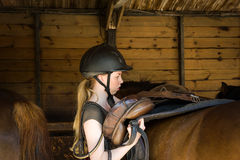 Girl saddle a horse. Close up of a young girl saddle a horse stock photos