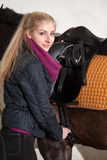 Girl saddles her horse Stock Image