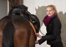 Girl saddles her horse Royalty Free Stock Photography