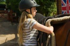 Girl saddling horse Royalty Free Stock Image