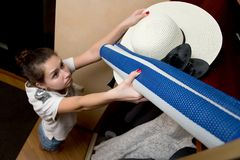 Girl sadly cleans summer accessories in a closet at the end of the beach season