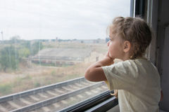 The girl sadly looking out the window of a train car Stock Images