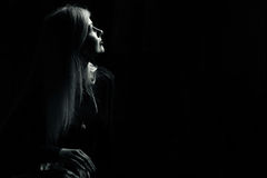 Girl in sadness. At dark room Stock Images