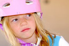 Girl in Safety Helmet. Close up of cute blonde girl in pink safety helmet looking apprehensive Royalty Free Stock Images