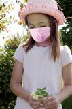 Girl with safety mask picks flowers