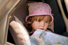 Girl in safety seat looking over window pane Stock Photography
