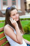 Girl said on his cell sitting on a bench. Royalty Free Stock Photos