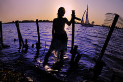 Girl and a sailboat. Silhouette of a girl looking at a sailboat stock images