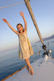 Girl on sailboat deck. Young girl dancing on the forward deck of a small sailboat stock image