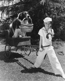 Girl in sailor suit pulling dog in basket Stock Photo