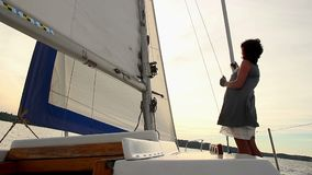 Girl sailor watching sunset on sailing yacht, summer activities. Stock footage stock footage