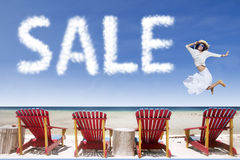 Girl and sale cloud jumping over beach chairs Royalty Free Stock Image