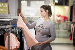 Girl at sale of fashion clothes in store. young woman is shopping on black Friday. girl chooses clothes in fashionable boutique. Girl at sale of fashion clothes Stock Image