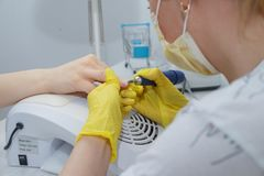 The girl in the salon nail service. Alignment of nails and treatment of nails with an electric machine. nt stock image