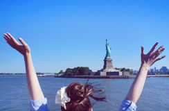 Girl salutes the Statue of Liberty Stock Photo