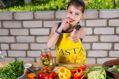 Girl Sampling Peppers and Giving Thumbs Up Royalty Free Stock Photos