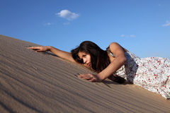Girl in sand. The young charming girl in a dress in sandy dunes against the sky in beams of the coming sun Stock Photo