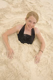 Girl in sand. Girl buried in the sand on the beach Royalty Free Stock Photos