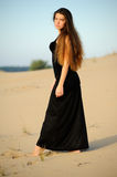 Girl on the sand. Girl in black dress on the sand Stock Photos