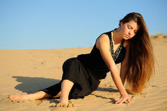 Girl and sand. Girl in black dress playing with sand Royalty Free Stock Photos