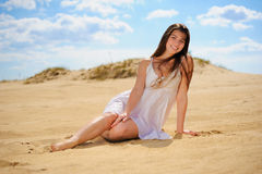 Girl on the sand. Girl in white dress sitting on the sand Royalty Free Stock Image