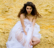 The girl on sand. In a white coverlet Stock Images