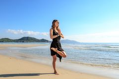 Girl, sand, balance posture in yoga, standing on one leg stock photos