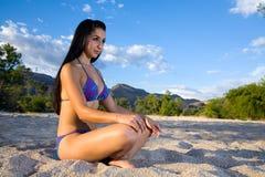 Girl in the sand in bikini Royalty Free Stock Photo