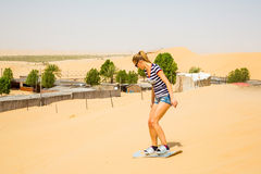 Girl sand boarding Stock Photo