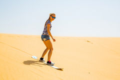 Girl sand boarding Stock Photography