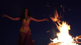 Girl in the sand dancing belly dancing near a bright campfire stock footage
