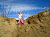 Girl on sand dune. Young girl on sand dune with blue sky and cloudscape background Stock Photography
