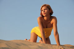 Girl in sand  looks at a decline. The beauty with red hair in a yellow dress against the blue sky in sandy dunes looks at a decline Stock Images