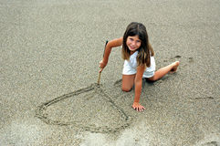 Girl in sand making hart. Girl at the beach drawing a hart in the sand with a stick stock photo