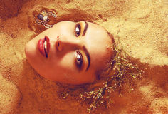 Girl in the sand. Portrait of a girl surrounded by sand royalty free stock image