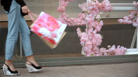 Girl in sandals goes past the boutiques with packages in hand. Young girl in sandals goes past the boutiques with packages in hand, close-up stock footage