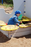 Girl in sandbox. Little girl in blue jeans coat and blue beret playing alone in sandbox with shovel Stock Image