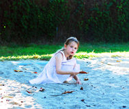 Girl in a sandbox. In the park in summer sunny day Royalty Free Stock Photos