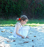 Girl in a sandbox. In the park in summer sunny day Royalty Free Stock Photo